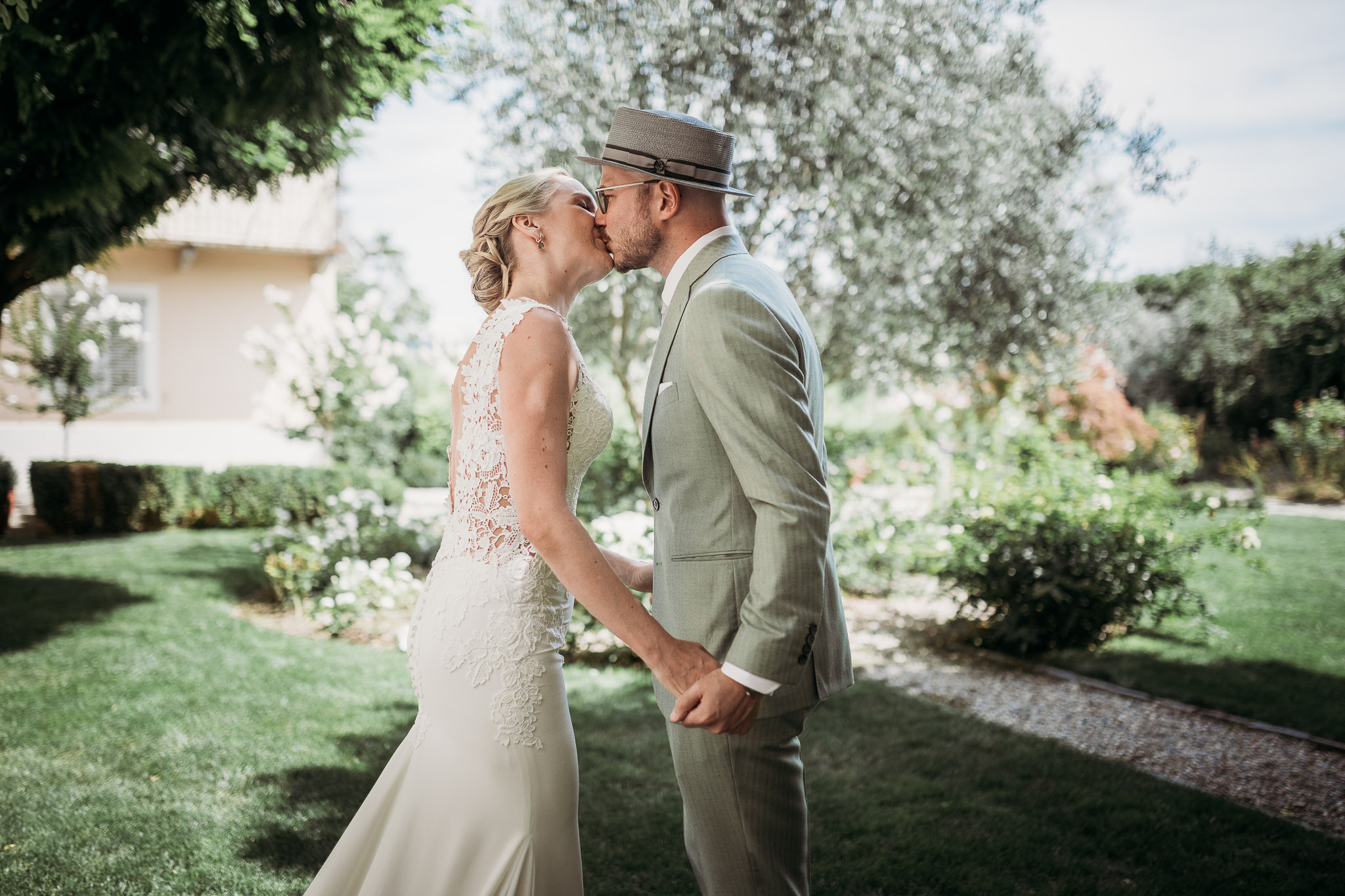 Bride and groom kissing in the courtyard during their first look at La Villa Hotel, Mombaruzzo