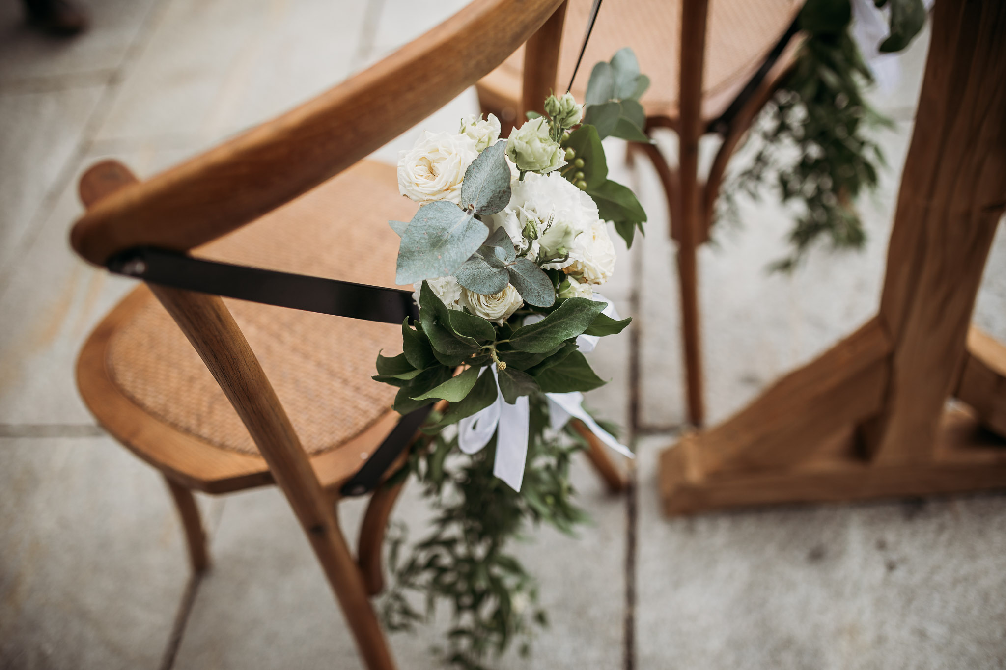 Decorated chairs with white flowers and greenery for wedding ceremony at La Villa Hotel, Mombaruzzo