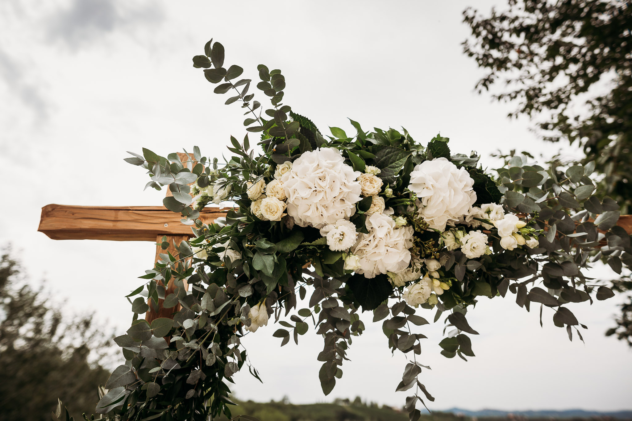 White carnation, olive and eucalyptus leaves wedding decor at La Villa Hotel, Mombaruzzo