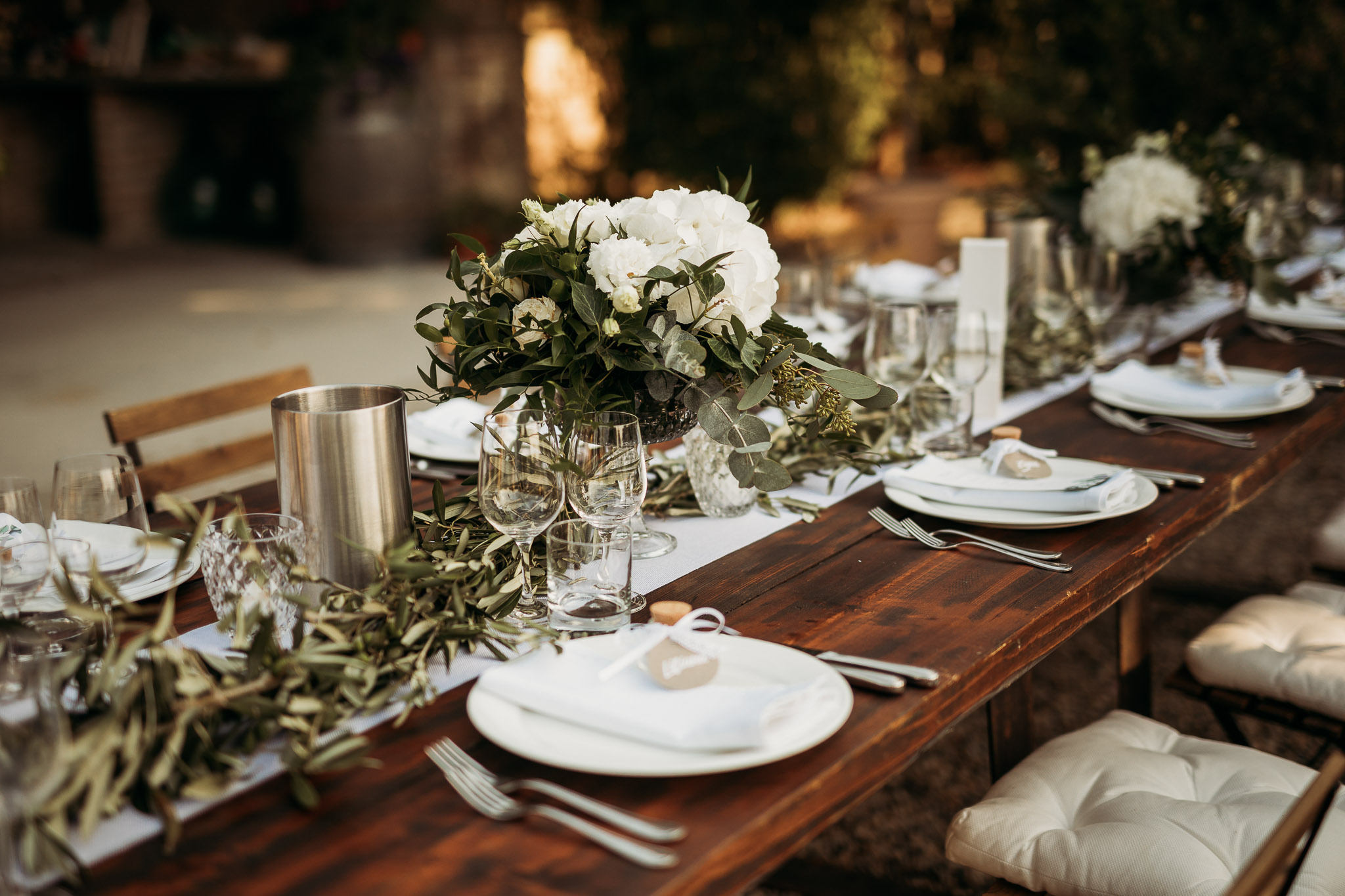 Table setting decor with white flowers, olive and eucapytus leaves at at La Villa Hotel, Mombaruzzo