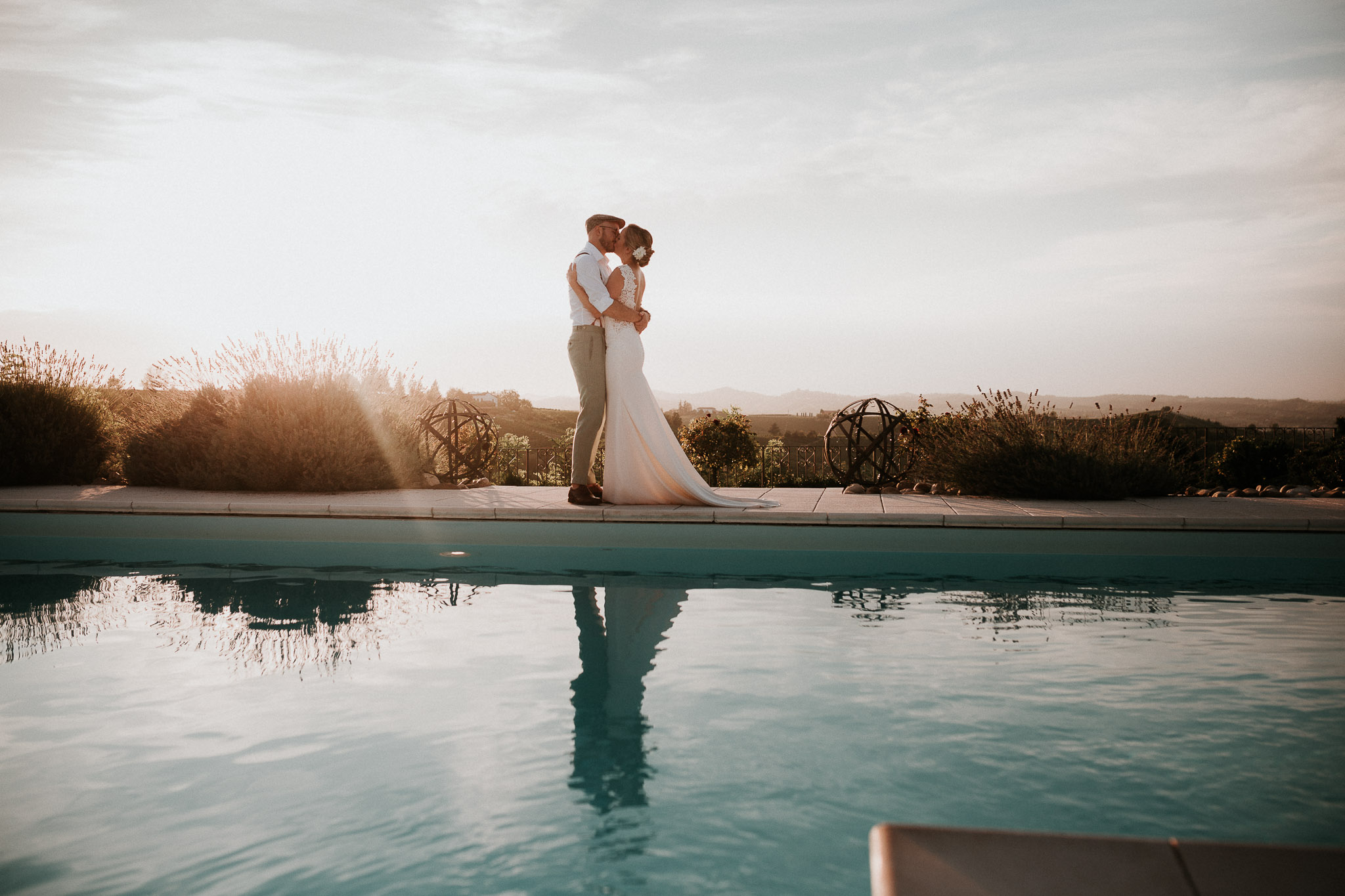 bride and groom hugging at sunset by the pool at La Villa Hotel, Mombaruzzo