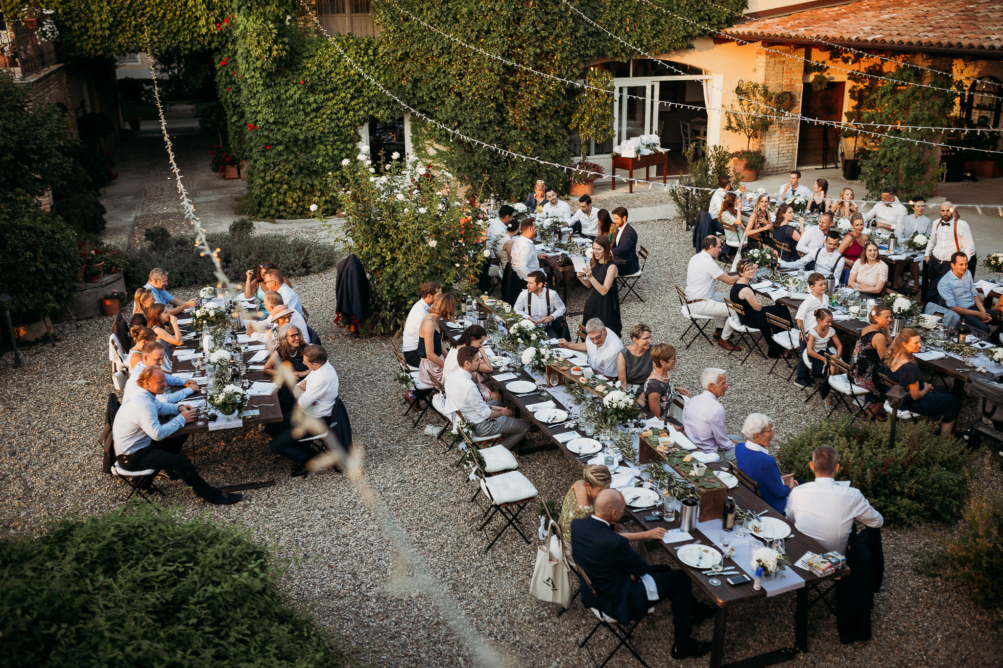 Courtyard wedding dinner with decorated tables and libght bulb festoons at La Villa Hotel, Mombaruzzo