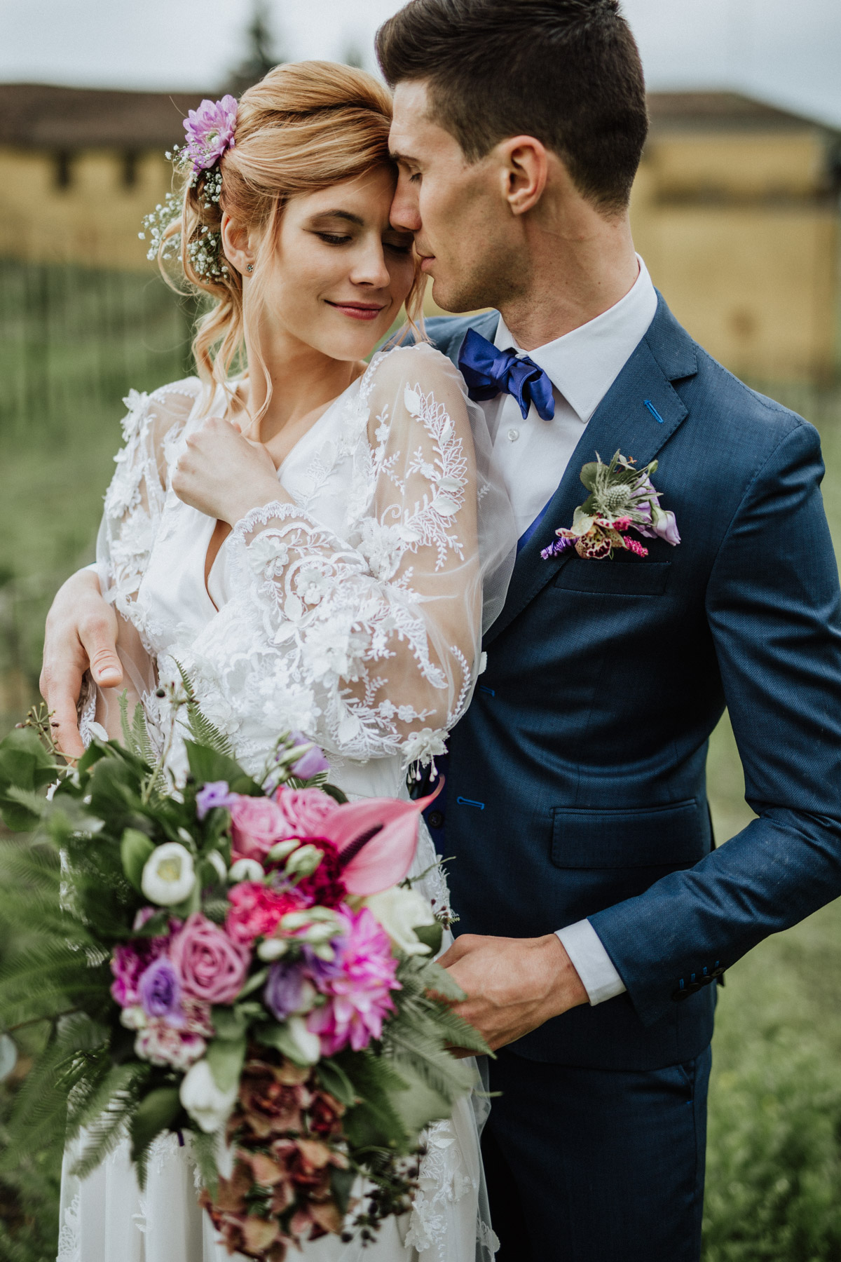 Romantic couple shot with lace bridal dress made by Marianna Lanzilli and orchid violet bouquet