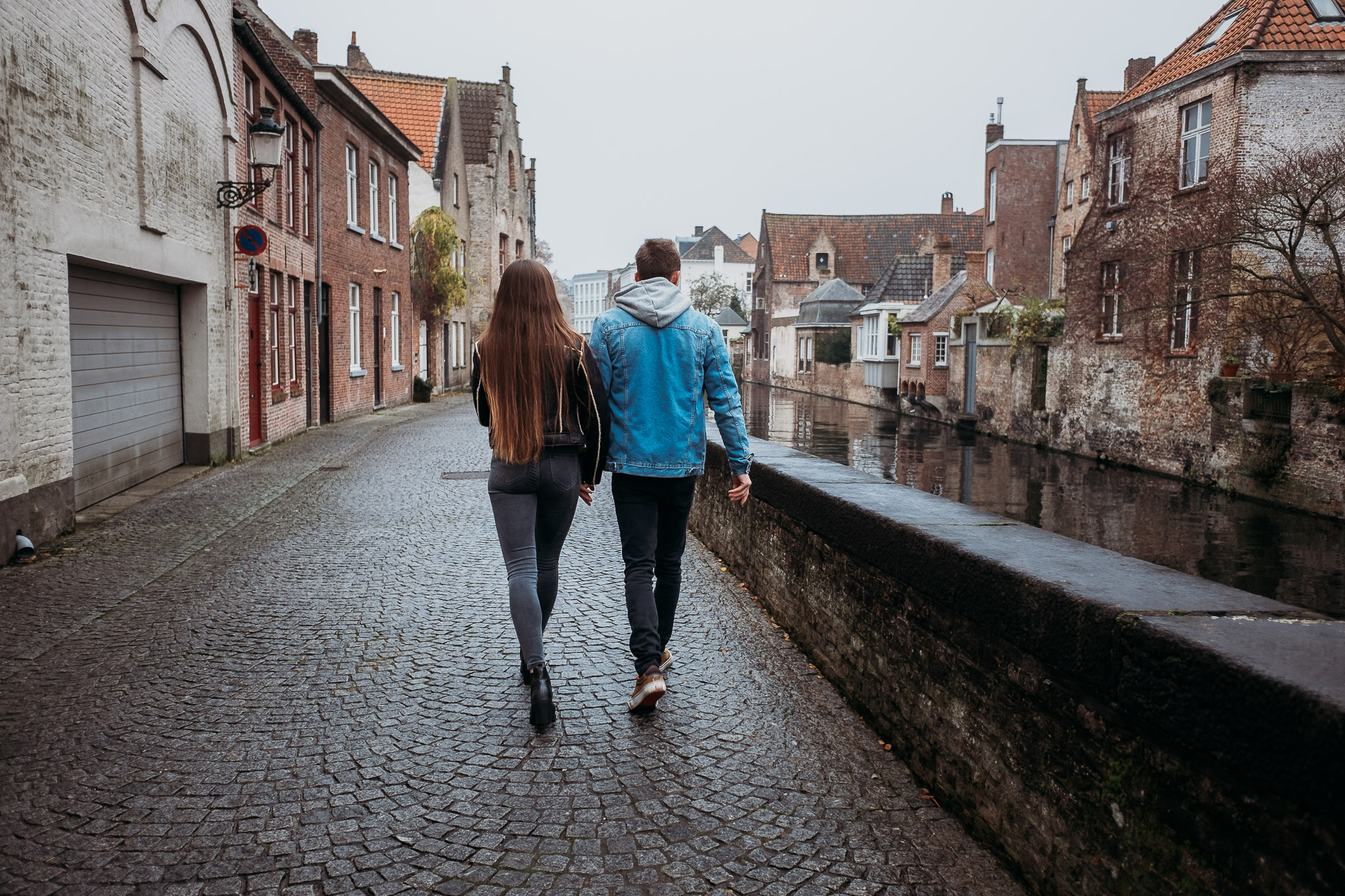 Couple strolling alongside the canal in Bruges, Belgium
