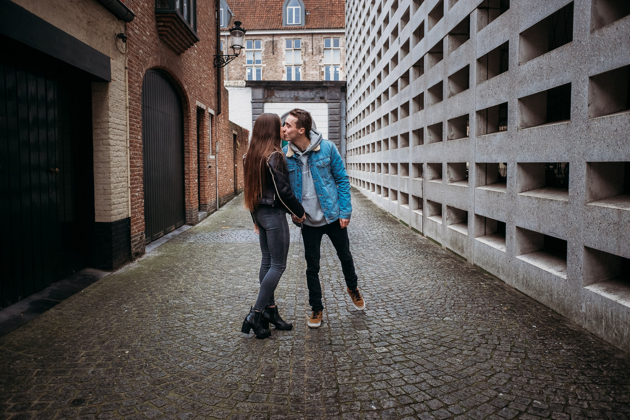 Couple holding hands in an alley in Bruges, Belgium