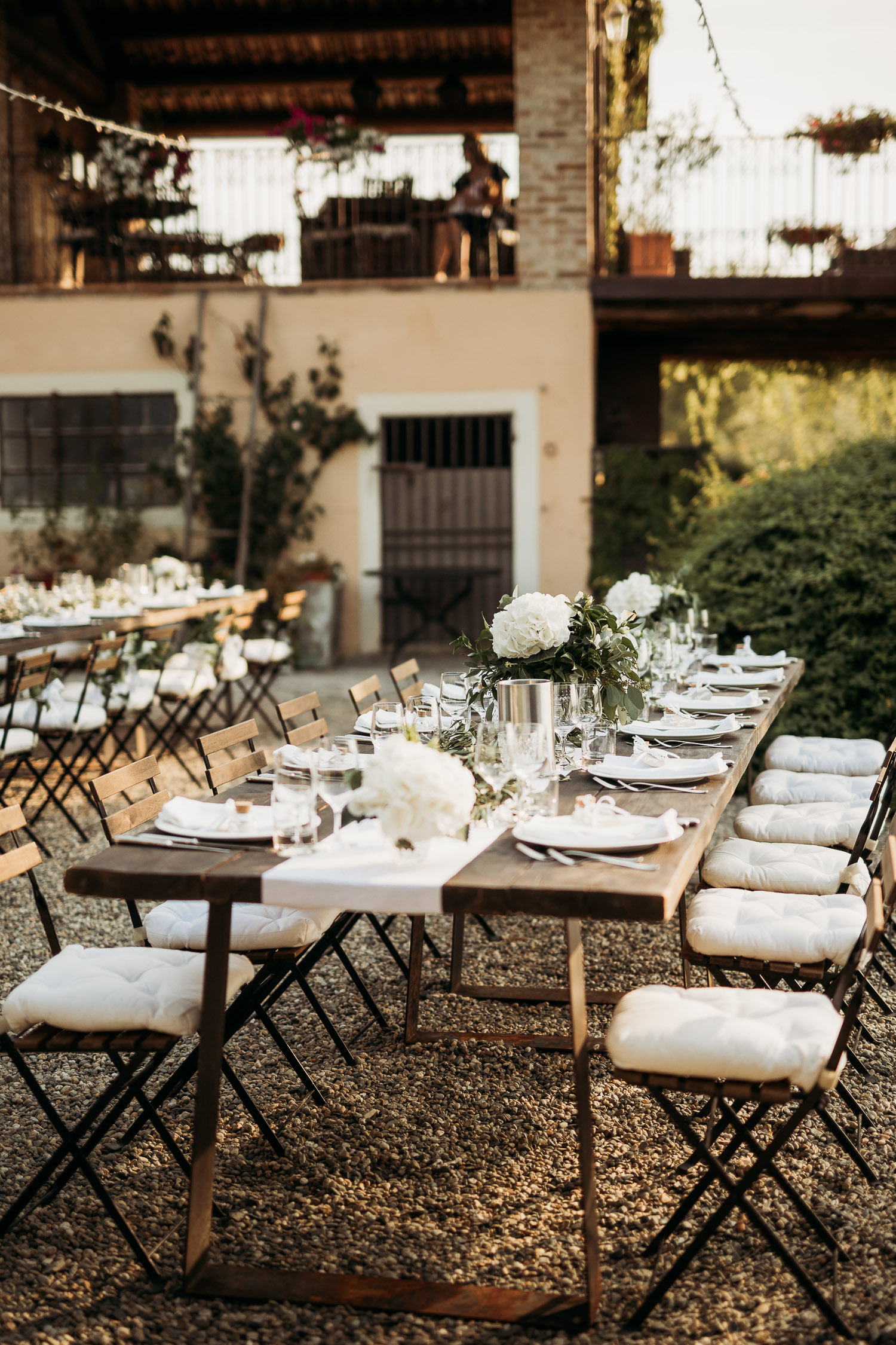 Rustic long table with white peonies and wood at La Villa Hotel in Mombaruzzo