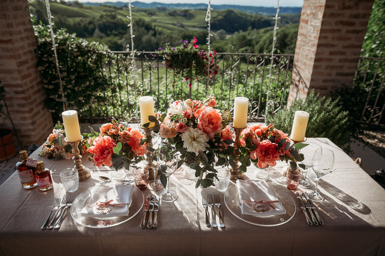 Elopement table with pink penoies and candles and view on the vineyards in Mombaruzzo