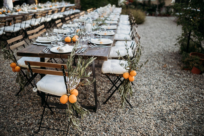 Tavoli da matrimonio in stile rustico con arance e foglie di ulivo