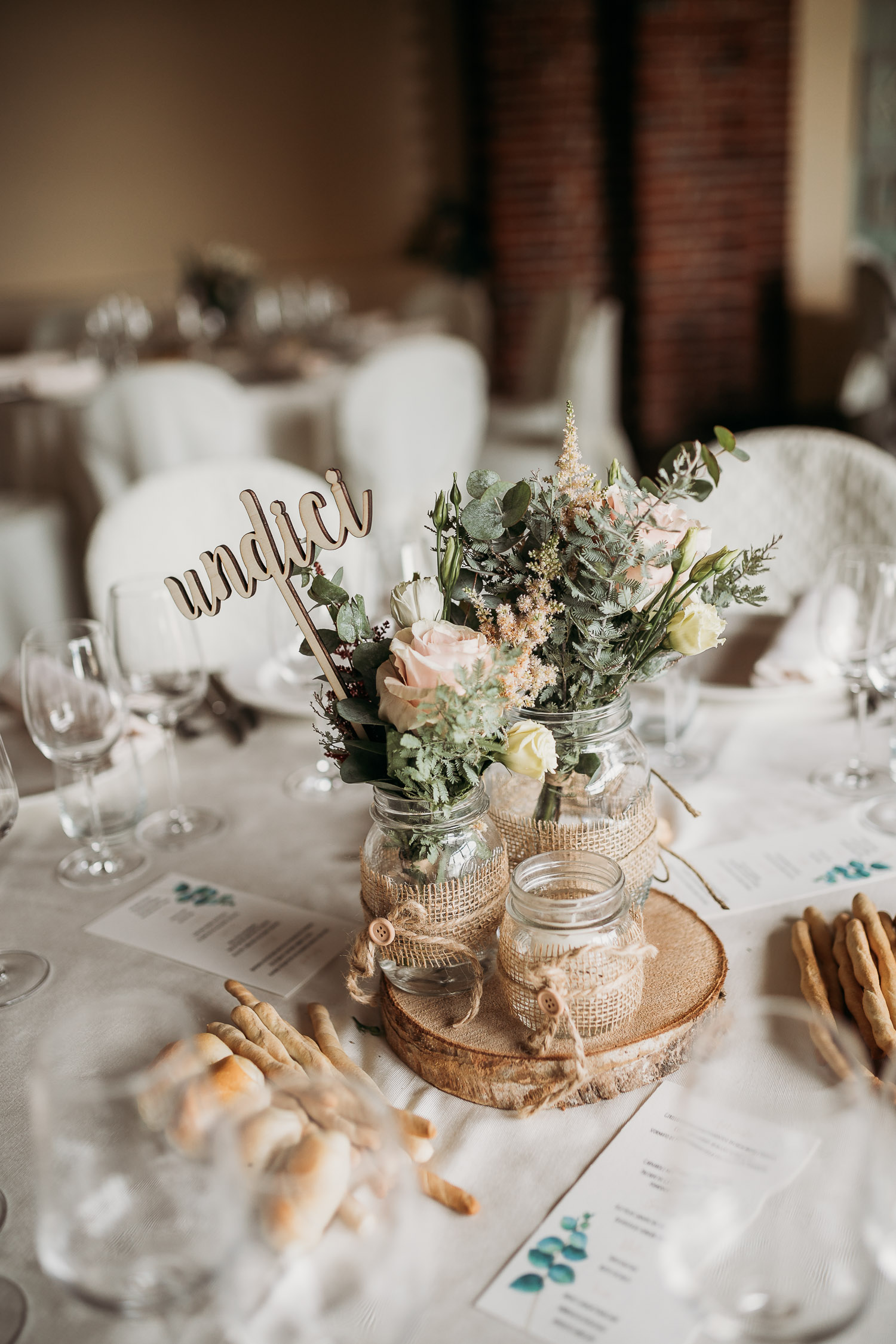 Rustic centerpiece with wooden numbers and romantic flowers at Tenuta Tamburnin